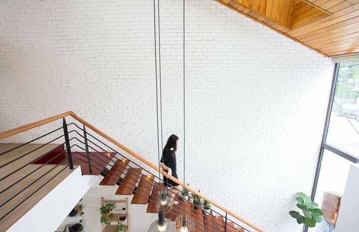 Cầu thang bậc gỗ bố trí sát tường phòng khách